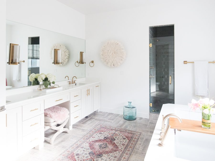 CC's sunday favorites loloi skye berry rug in a master bathroom with white cabinets and gold lighting and hardware with wood grain tile floors-1
