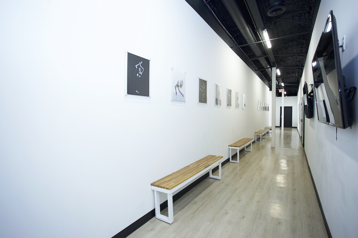 elite dance studio hallway with wooden benches, white walls and black and white photography with tvs
