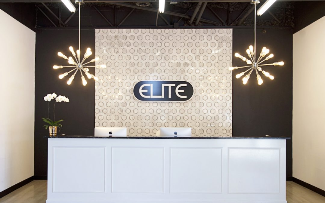 elite dance studio front desk with a white front desk and gorgeous chandeliers