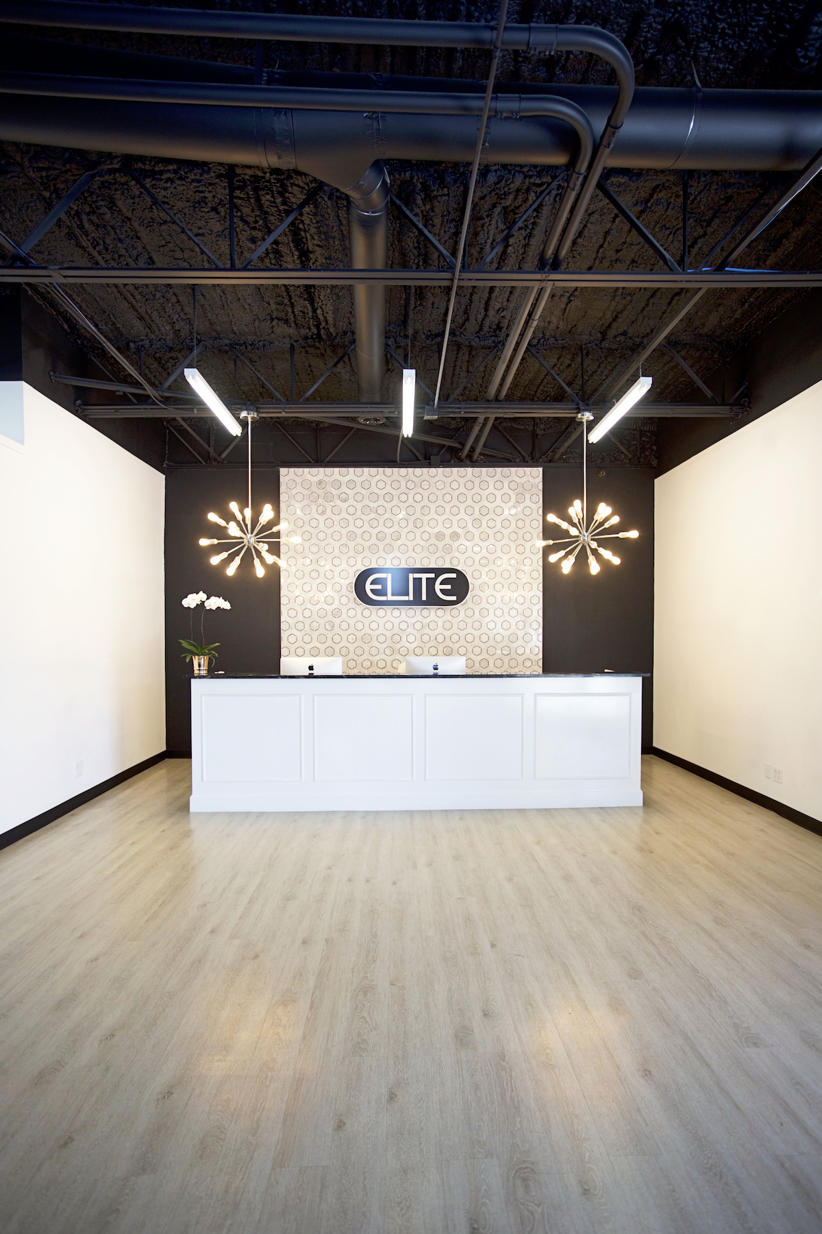 elite dance studio far back shot of the entire front desk, hexagon tile backsplash and sputnik chandeliers