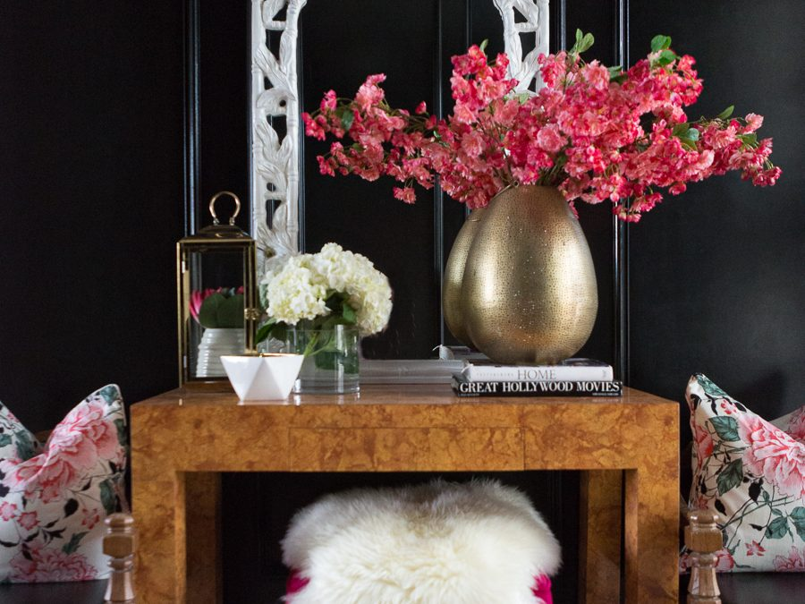 entry way table with gold vase, flowers, flower pillows and a black accented wall