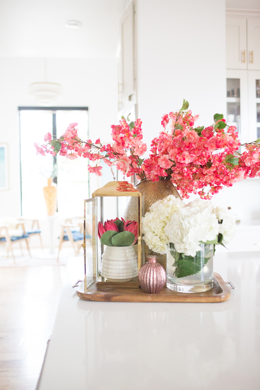 5 Tips to Decorate Your Home with Drew Barrymore Flower Home white quartz waterfall kitchen island with gold bar stools and ann sacks patterned honeycomb backsplash with gold kitchen lanterns and pink flowers styled in a kitchen