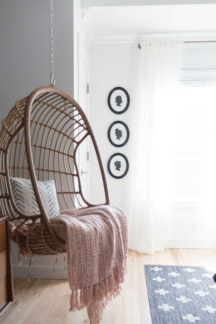 CC and Mike Teen Hangout Room Reveal with Joybird Sectional-3 woven hanging chair and easy $5 DIY silhouette frames on a white painted wall