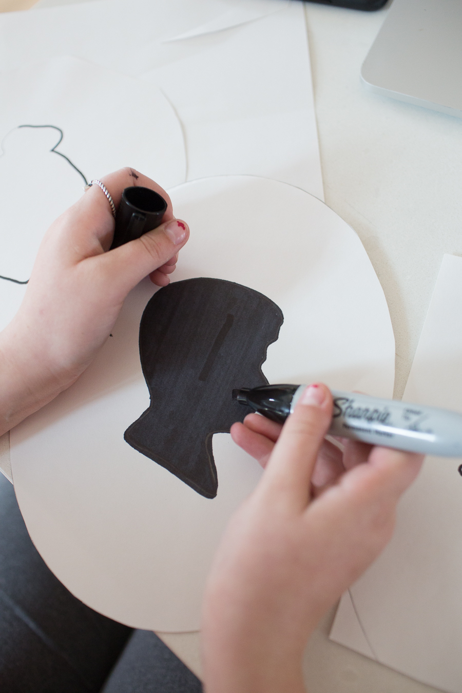 coloring in a boy's silhouette with black marker