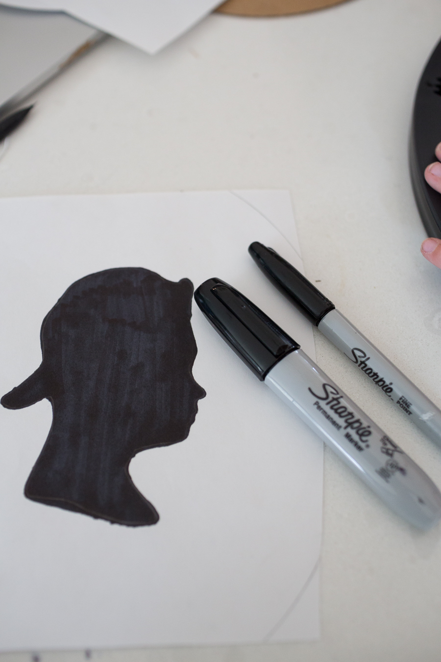 a black silhouette of a teenage boy with a backwards hat