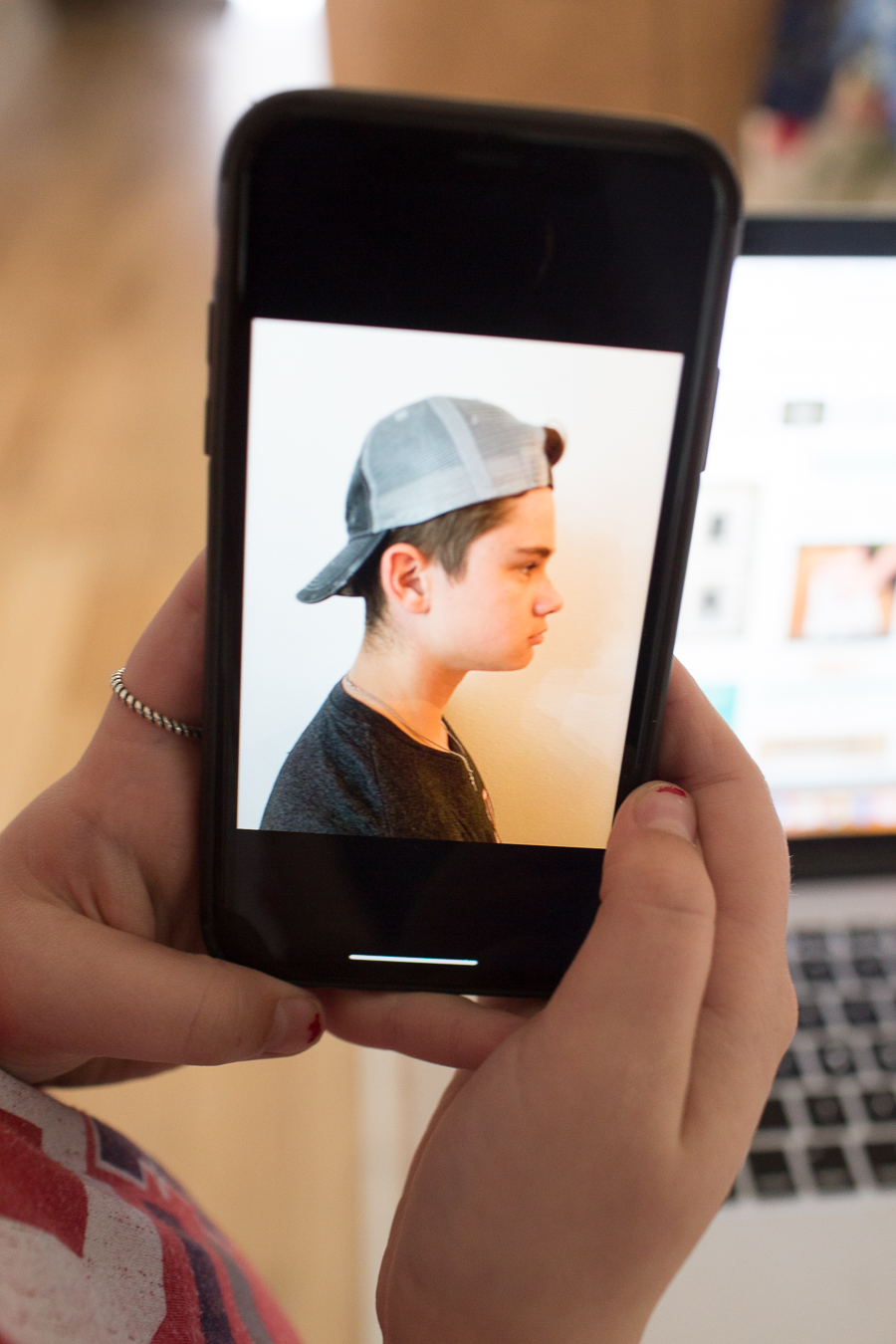 holding up an image on an iphone of a teenage boy profile