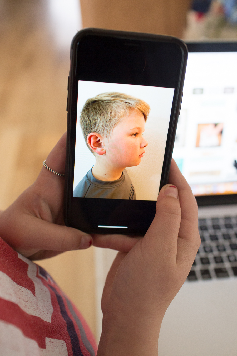 profile view of a blonde boy on an iphone