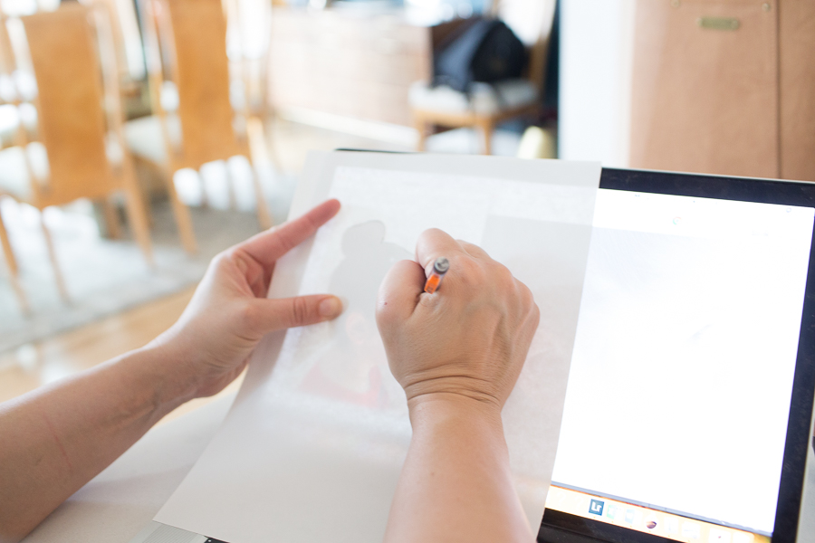 a person tracing over the laptop screen with paper and a pencil