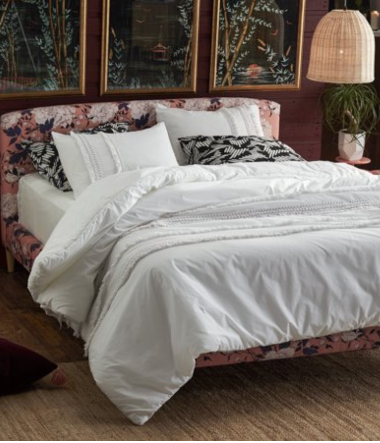 5 Tips to Decorate Your Home with Drew Barrymore Flower Home pink tufted velvet headboard and bed with white embroidered sheets white duvet set from Walmart