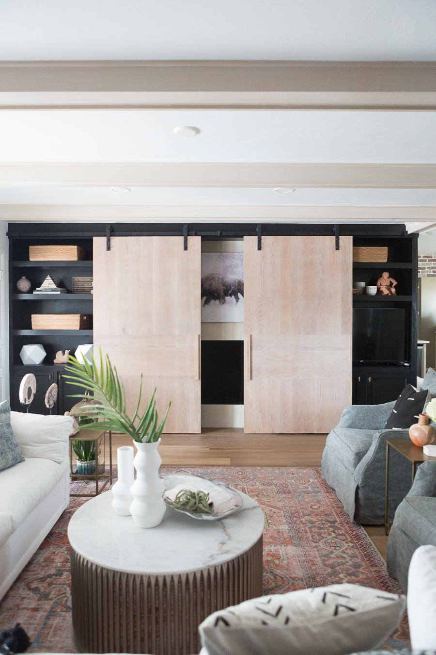 CC and Mike Kane Project Remodel Reveal natural wood sliding barn doors in a living room model with black open shelving