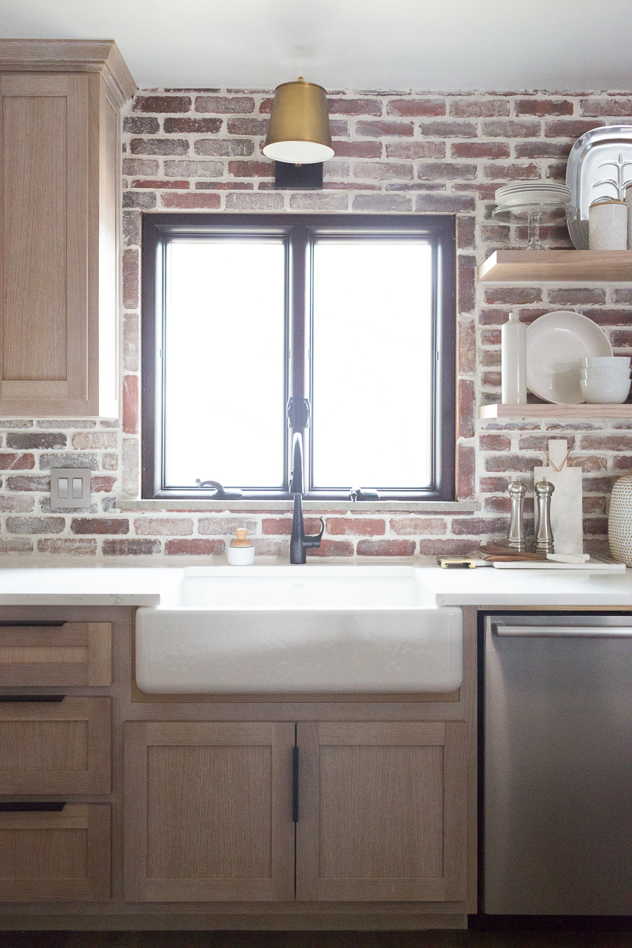 CC and Mike Kane Project Remodel Reveal brick kitchen bacskplash with a white farmhouse sink and black faucet rift sawn white oak cabinets with black hardware