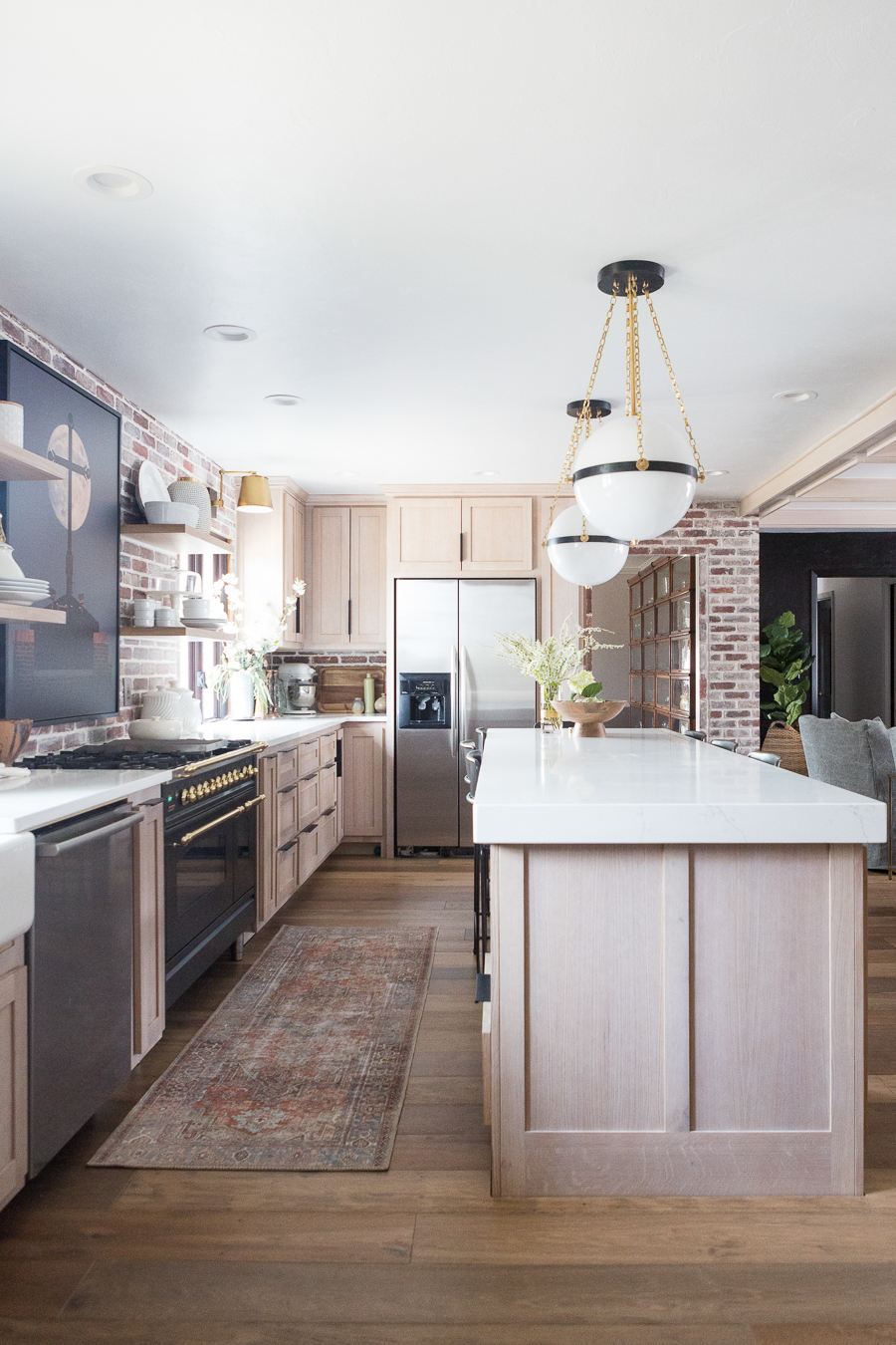 Image of: Cc And Mike Kane Project Remodel Reveal Rift Sawn White Oak Wood Kitchen Cabinets With Marble Countertops Arteriors Pendant Lighting Black Hardware Black Stove With Gold Hardware Terracotta Loren Kitchen Runner