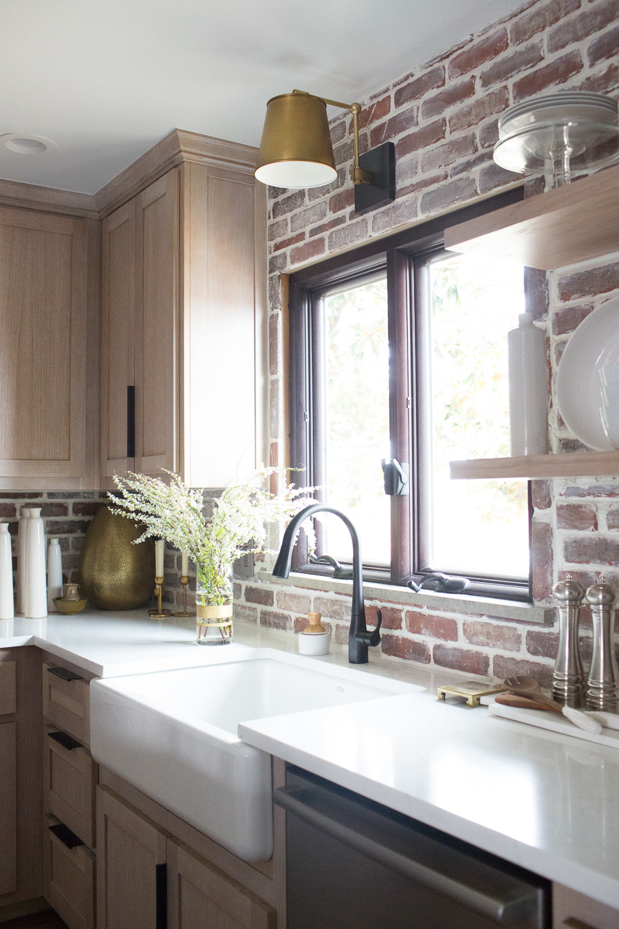 Image of: Cc And Mike Kane Project Remodel Reveal Brick Kitchen Bacskplash With A White Farmhouse Sink And Black Faucet Rift Sawn White Oak Cabinets With Black Hardware 7 Cc Mike
