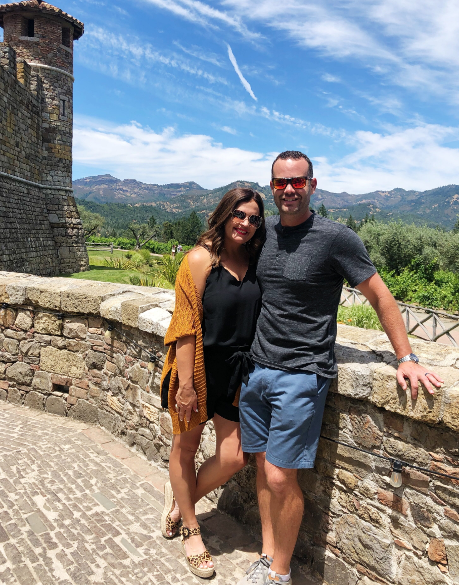 cc and mike standing in front of the beautiful mountain views with a castle