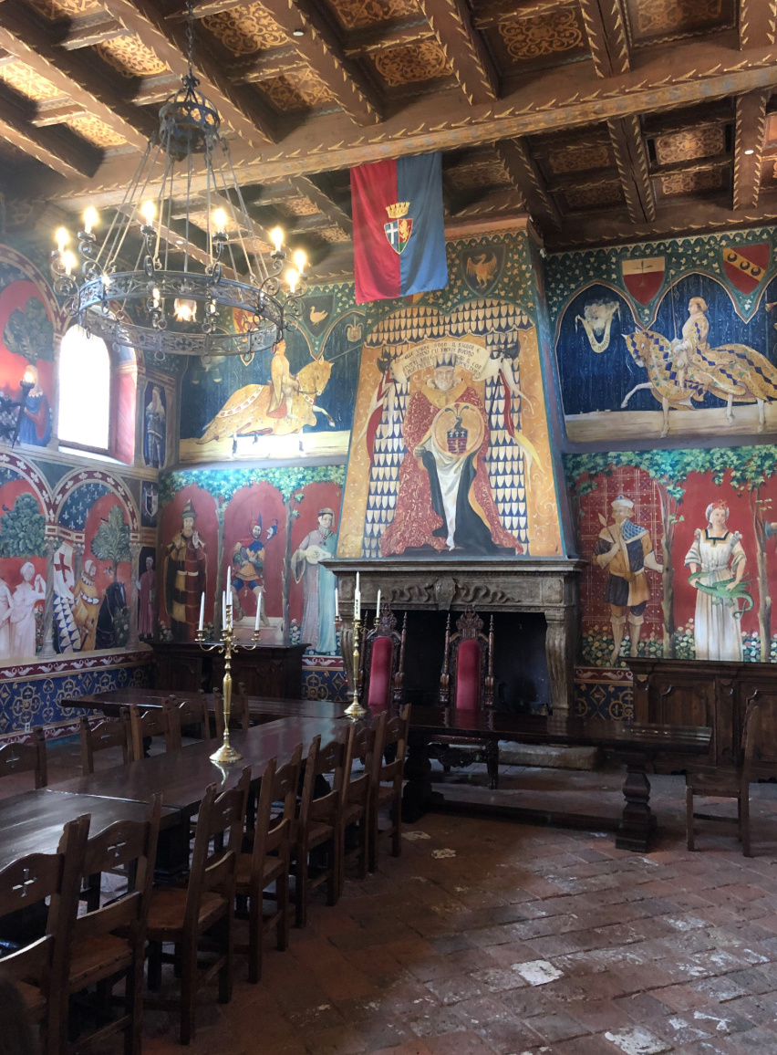 inside the gorgeous castle with long wooden dining tables and multiple colorful murals