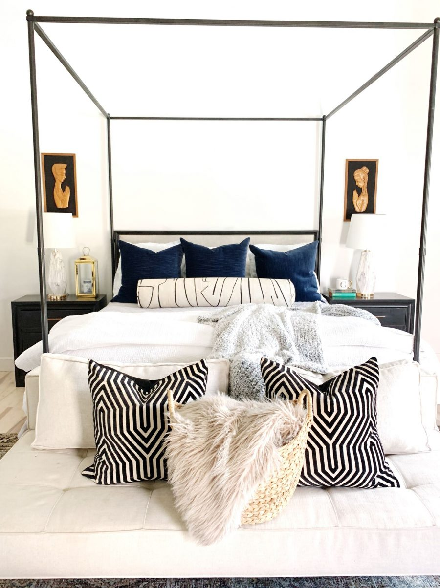Coastal Master Bedroom Design with Walmart Home Frenchie in a seagrass basket in front of an iron canopy bed