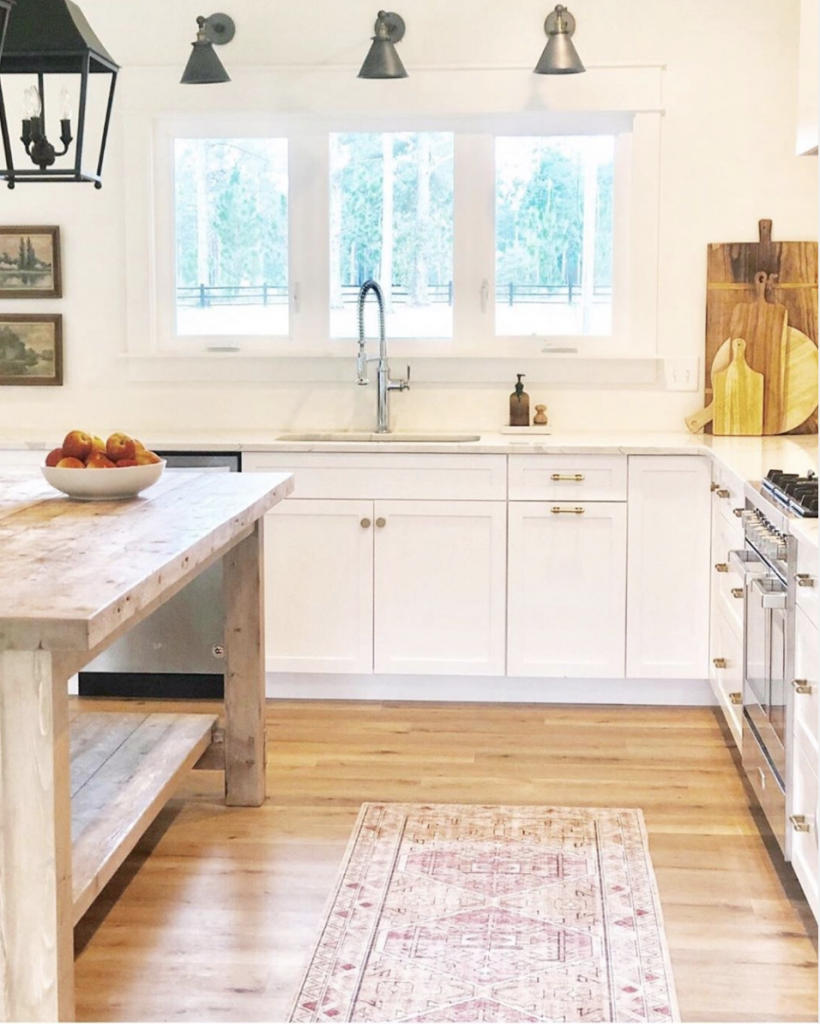 CC and Mike the SHOp labor day sales gold blush skye rug white kitchen cabinets with an all wood butcher block island and black lantern light fixtures