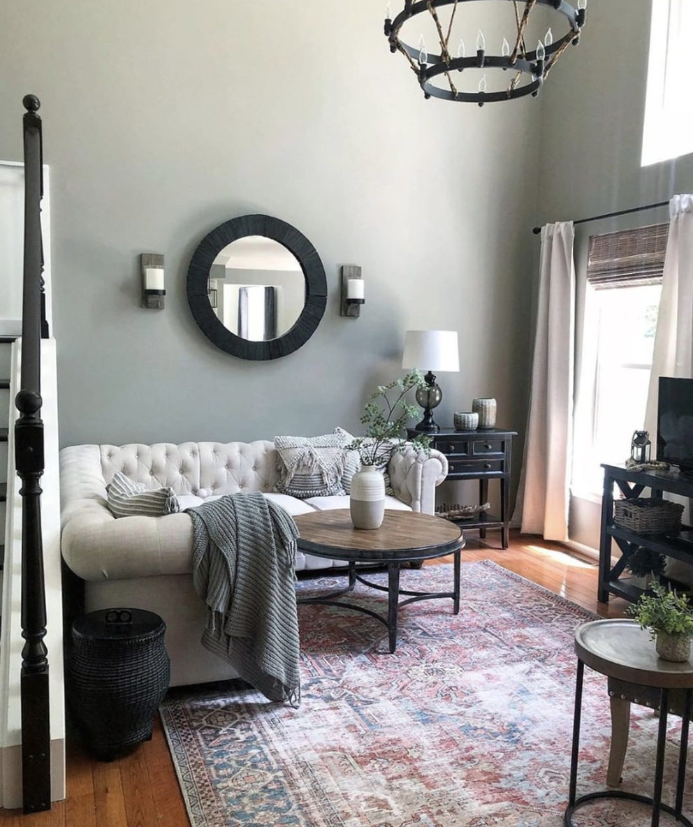 CC and Mike labor day sales terracotta loren rug in a living room with a gray chesterfield couch sofa and a sage green wall color with a round wood coffee table