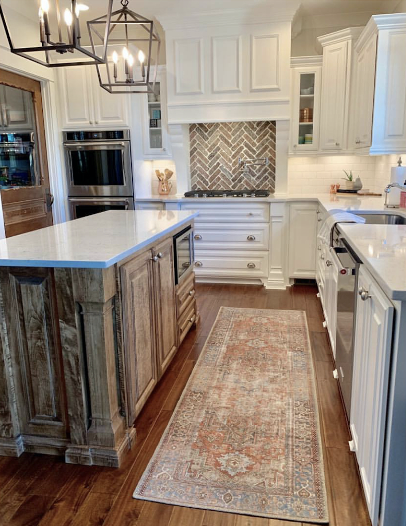 CC and Mike labor day sales terracotta loren rug in a beautiful white kitchen with natural wood island and quartz countertops and white kitchen cabinets with brick backsplash and silver hardware
