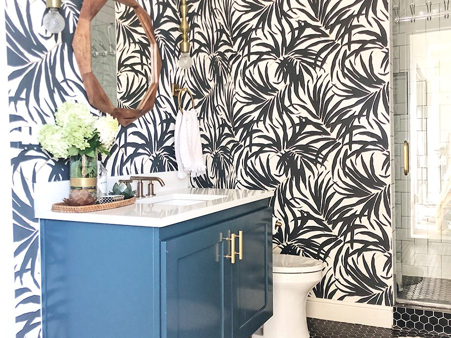 Vintage Chic Bathroom Update black hexagon floors with a green floating vanity and a wood mirror palm frond wallpaper