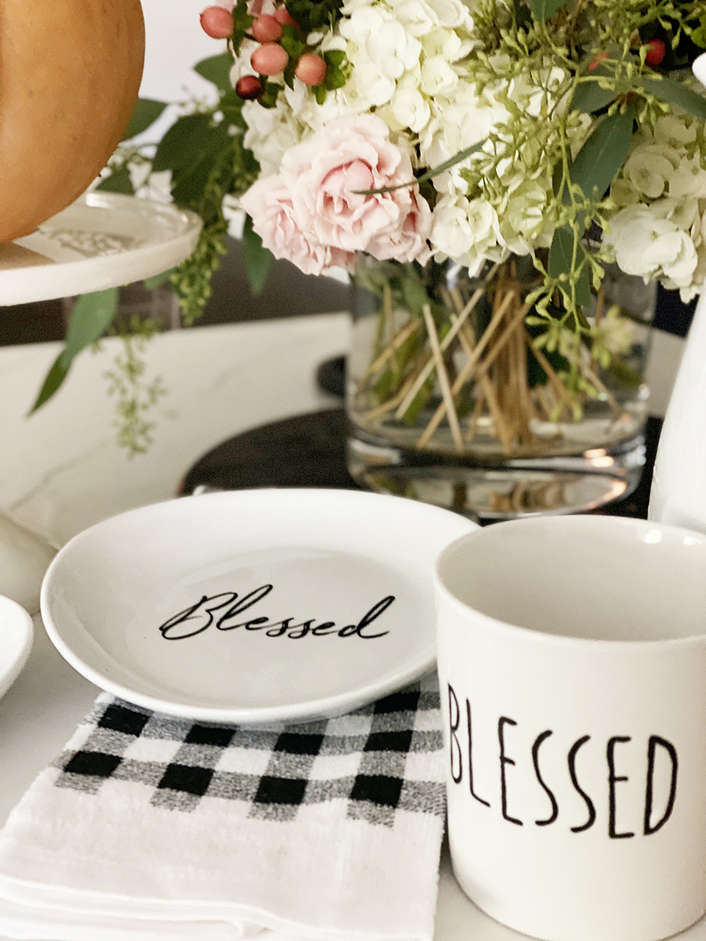 Affordable Fall Front Porch and Tabletop Decor Ideas buffalo plaid dish towel pioneer woman cake stand with pumpkin on top blessed coffee mug and plat