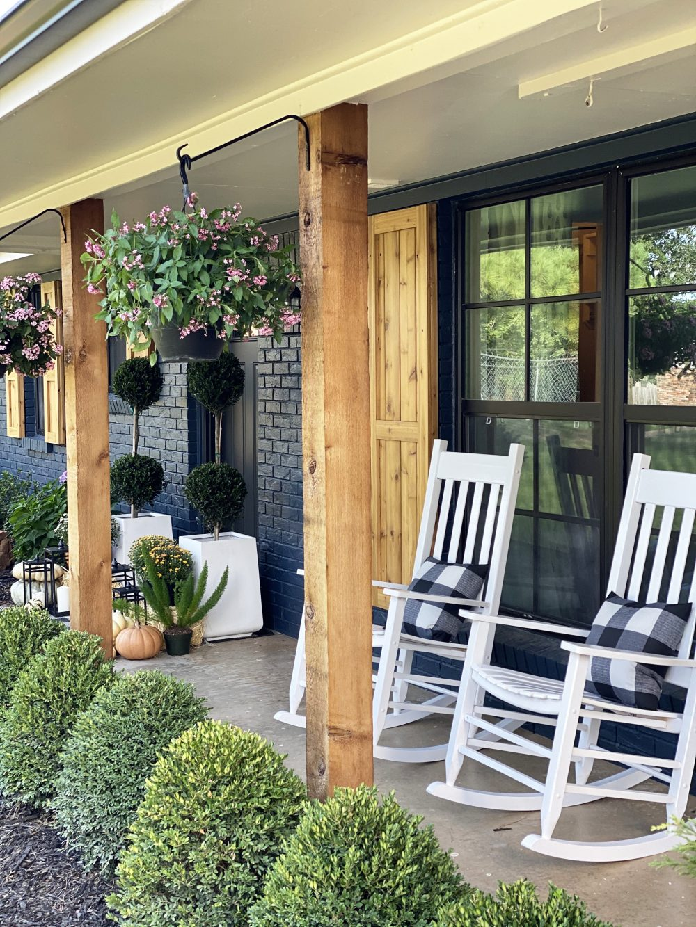 Affordable Fall Front Porch and Tabletop Decor Ideas white rcokers on front porch of a navy house with cedar shutters fall styling