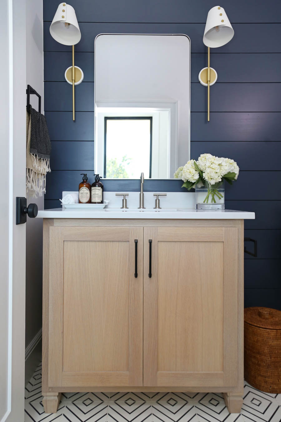 Cc And Mike Frisco I Project Reveal Navy Shiplap Wall With White Oak Vanity In A Bathroom With Silver Mirror And Brass And White Sconces Black Hardware Cc Mike
