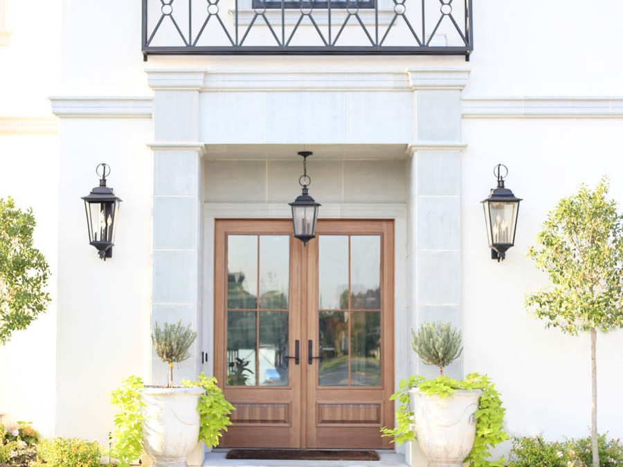 CC and Mike Frisco I Project Reveal-2 white European stucco exterior with cast stone around wooden door and topiary planters