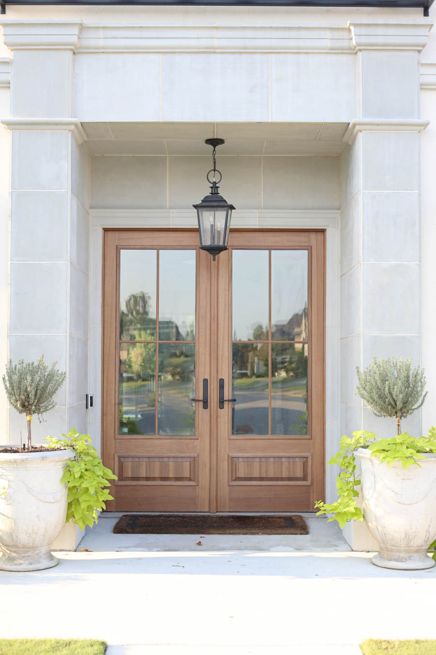 CC and Mike Frisco I Project Reveal-2 white European stucco exterior with cast stone around wooden door and topiary planters beautiful wooden front doors