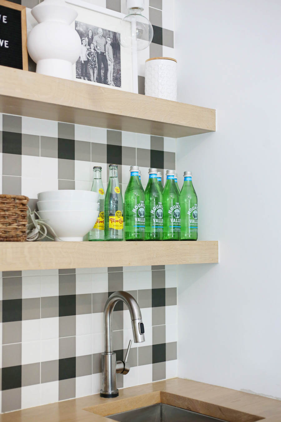 CC and Mike Frisco I Project Reveal black and white buffalo plaid check tile with open wood shelving in a game room bar stainless steel sink with butcher blog countertops