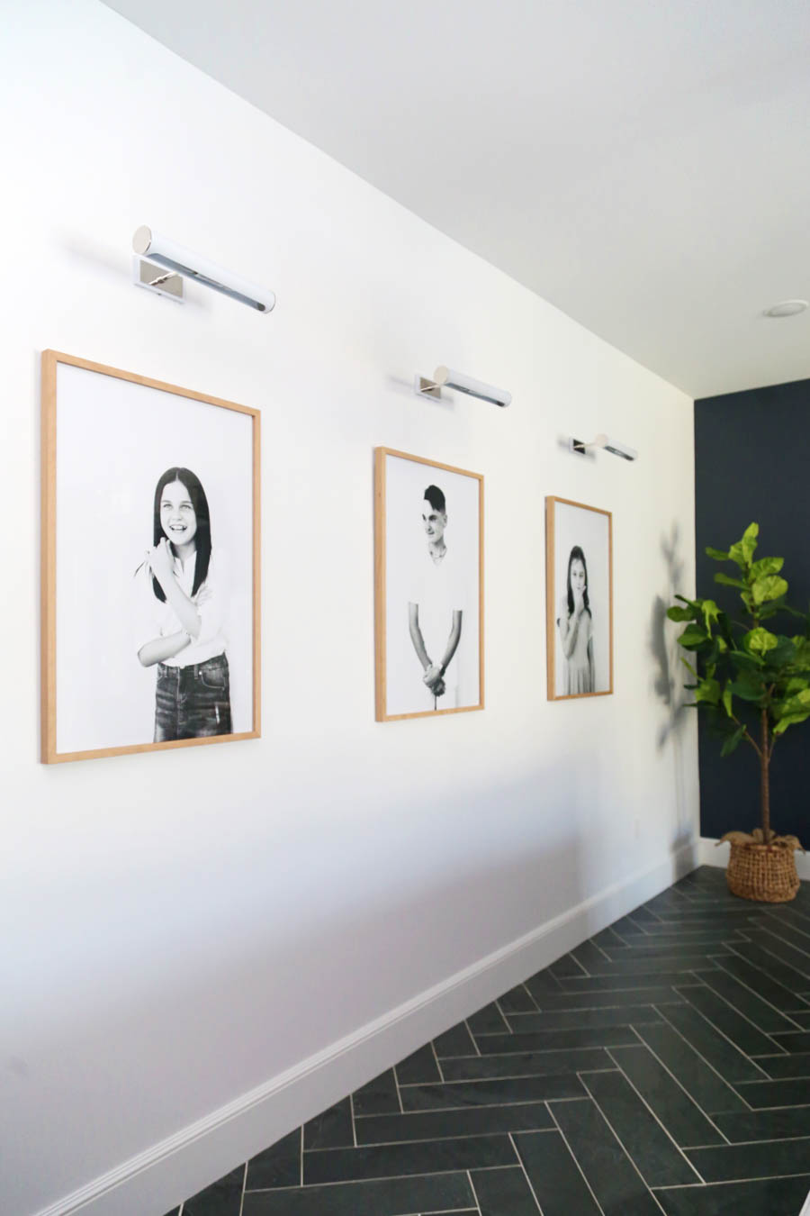 CC and Mike Frisco I Project Reveal large scale framed kids pictures in a game room with library sconces and a black accent wall and black tile floors