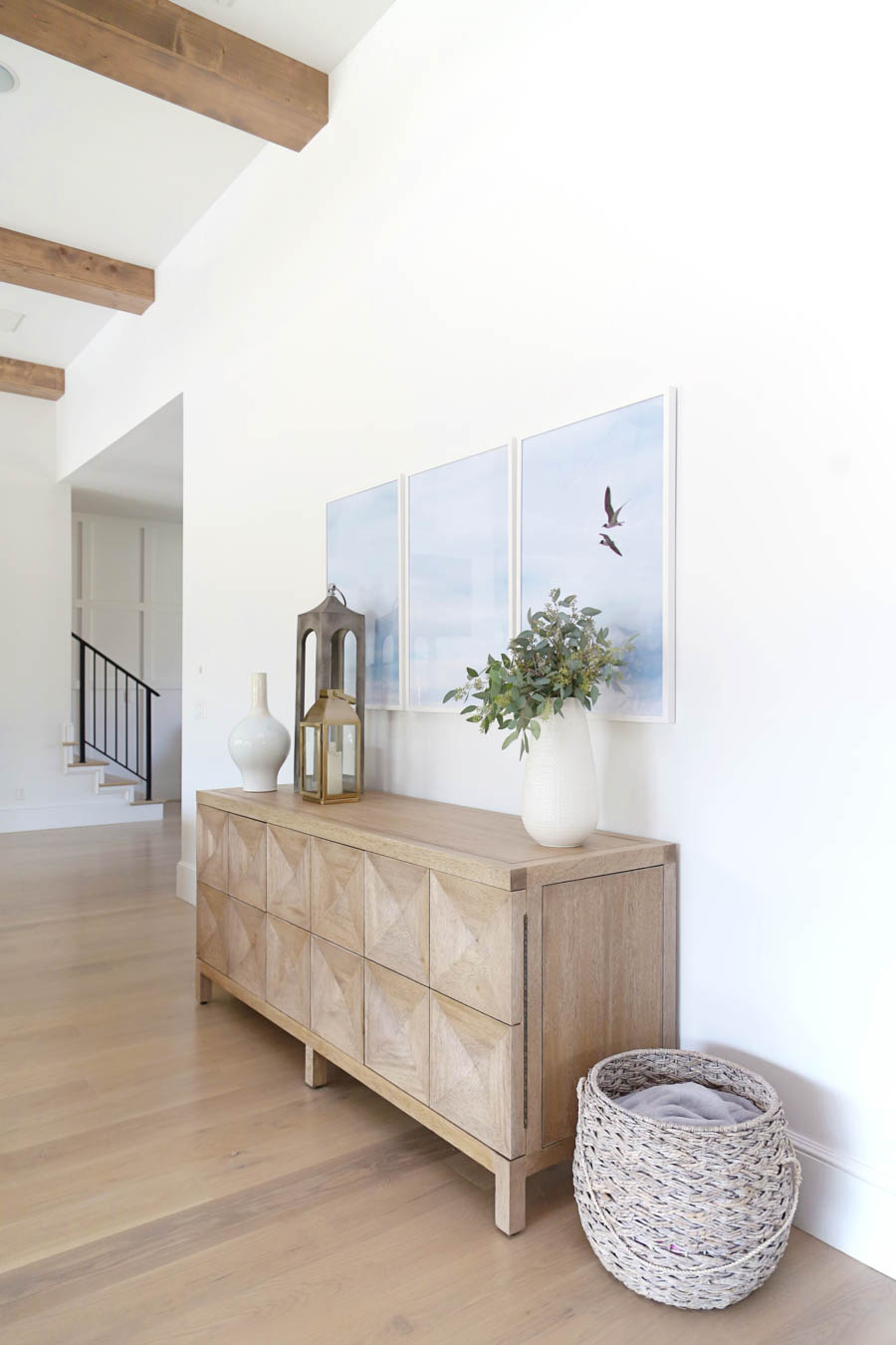 CC and Mike Frisco I Project Reveal white wall with three birds =large triptych wall art gold pottery barn lantern and wood sideboard from cc and mike the shop