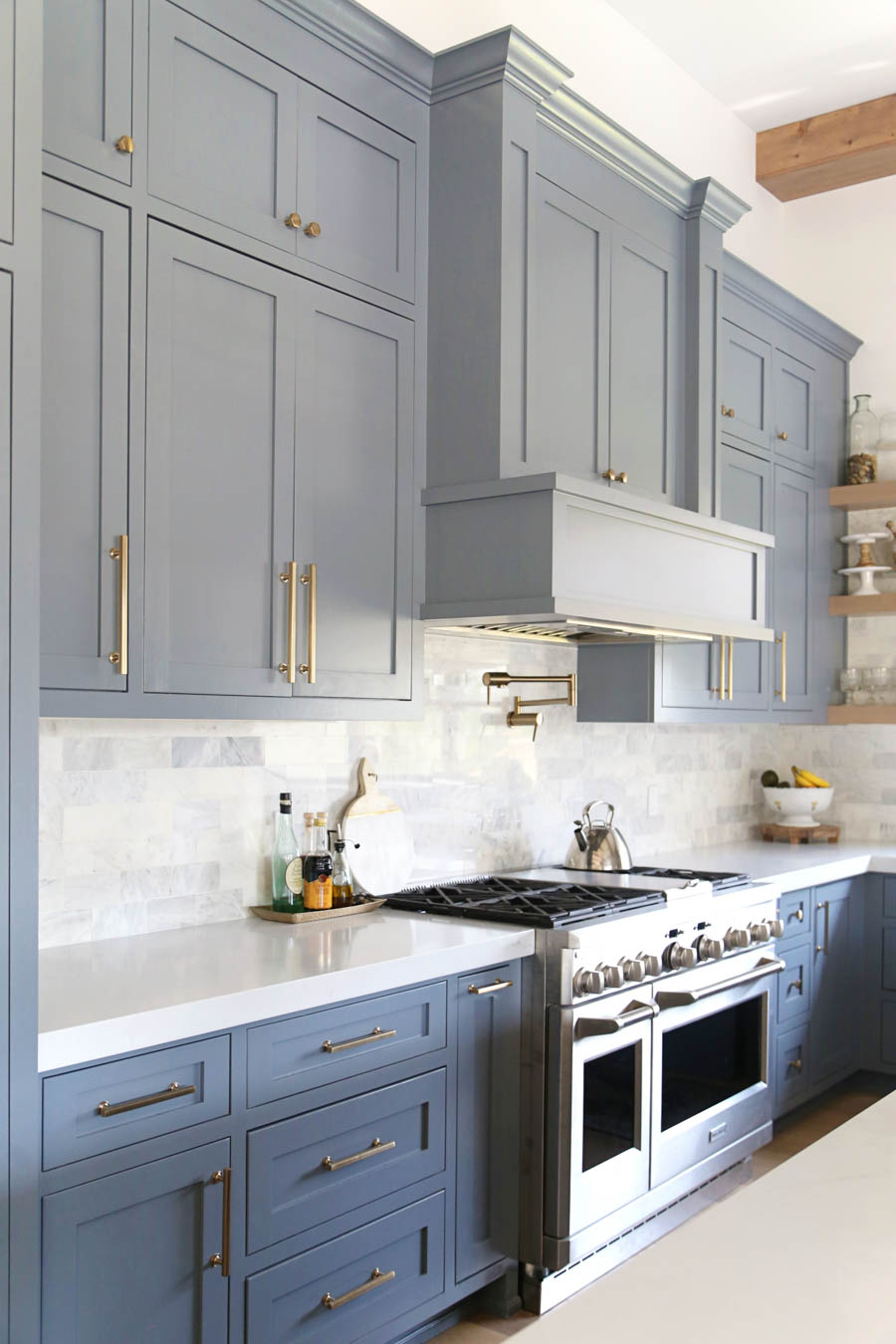 CC and Mike Frisco I Project Reveal-63 gray kitchen island and cabinets with wood bar stools quartz countertops and gold lanterns large kitchen window with gold sconces
