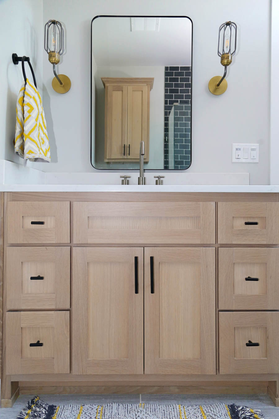 CC and Mike Frisco I Project Reveal black slate tile floors in a boys bathroom design with natural wood cabinets black hardware Franco bathroom mirror and gold and black sconces from CC and Mike THE SHOP