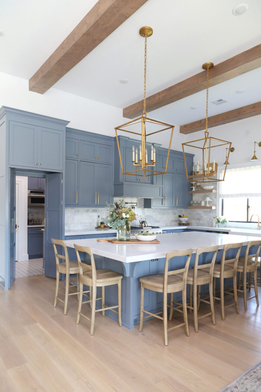 CC and Mike Frisco I Project Reveal-63 gray kitchen island and cabinets with wood bar stools quartz countertops and gold lanterns large kitchen window with gold sconces hidden pantry