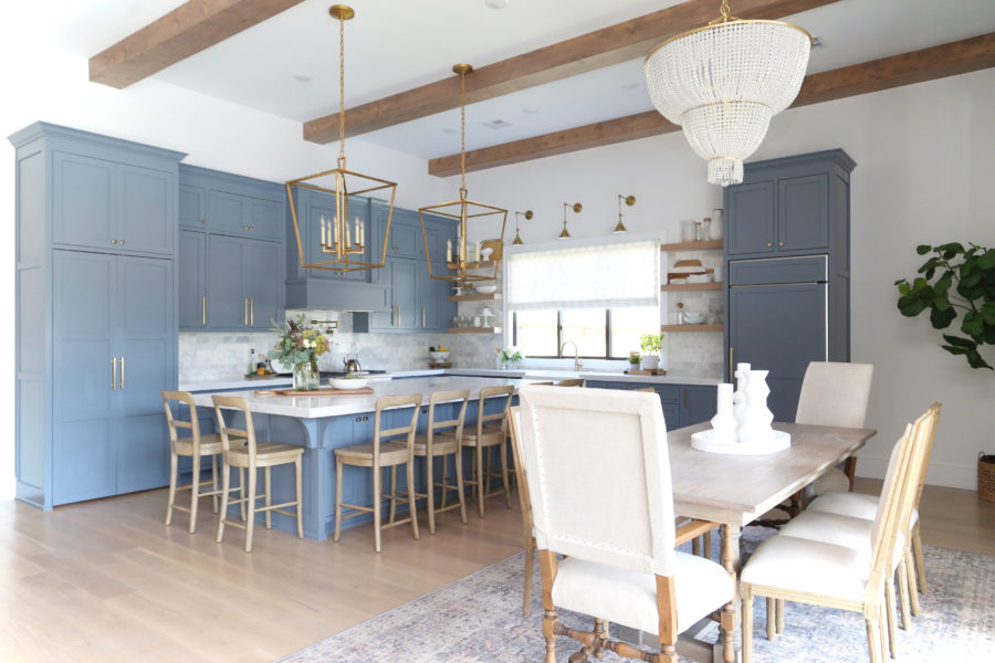 CC and Mike Frisco I Project Reveal-63 gray kitchen island and cabinets with wood bar stools quartz countertops and gold lanterns large kitchen window with gold sconces hidden pantry open floorpan dining room to gray kitchen with gold hardware wood farmhouse table and gold beaded chandelier