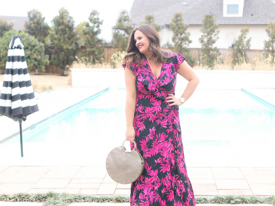 15 Must Have Walmart Fashion Items for Spring Carissa Miller standing by a rectangular pool with hot tub and black and white umbrella in a black and pink palm print wrap dress by Sofia Vergara Walmart