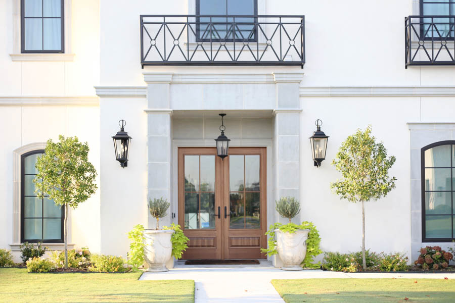 CC and Mike Frisco I Project Reveal-2 modern European exterior stucco exterior with cast stone around the entryway wood door pendant drop lantern