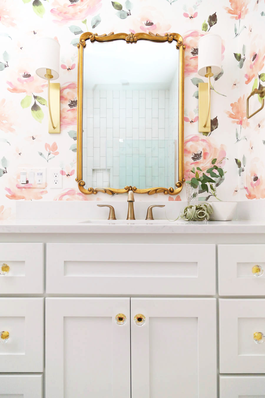CC and Mike Frisco I Project Reveal modern girls bathroom design with floral Anthropologie wallpaper white cabinets gold Tolouse mirror acrylic and gold hardware on a white bathroom vanity and white hexagon floors