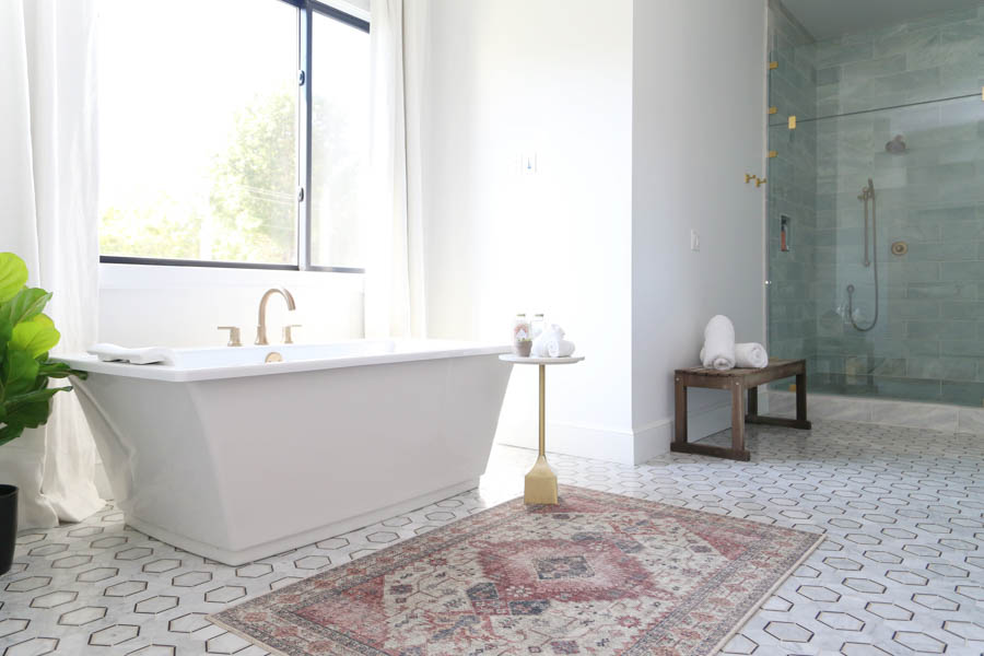 How-to-Update-Your-Rugs-for-Spring pink and gold blush Skye rug on a black and gold  honeycomb marble floor with a large Kohler soaking tub