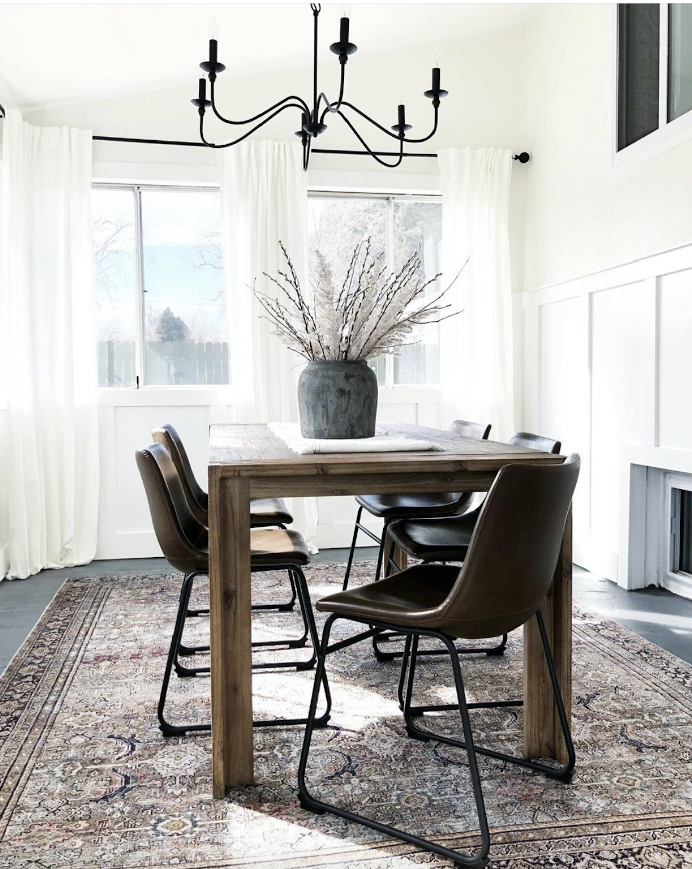 How-to-Update-Your-Rugs-for-Spring olive charcoal Layla with a wood Dining room table black spindle dining chairs and upholstered linen dining chairs