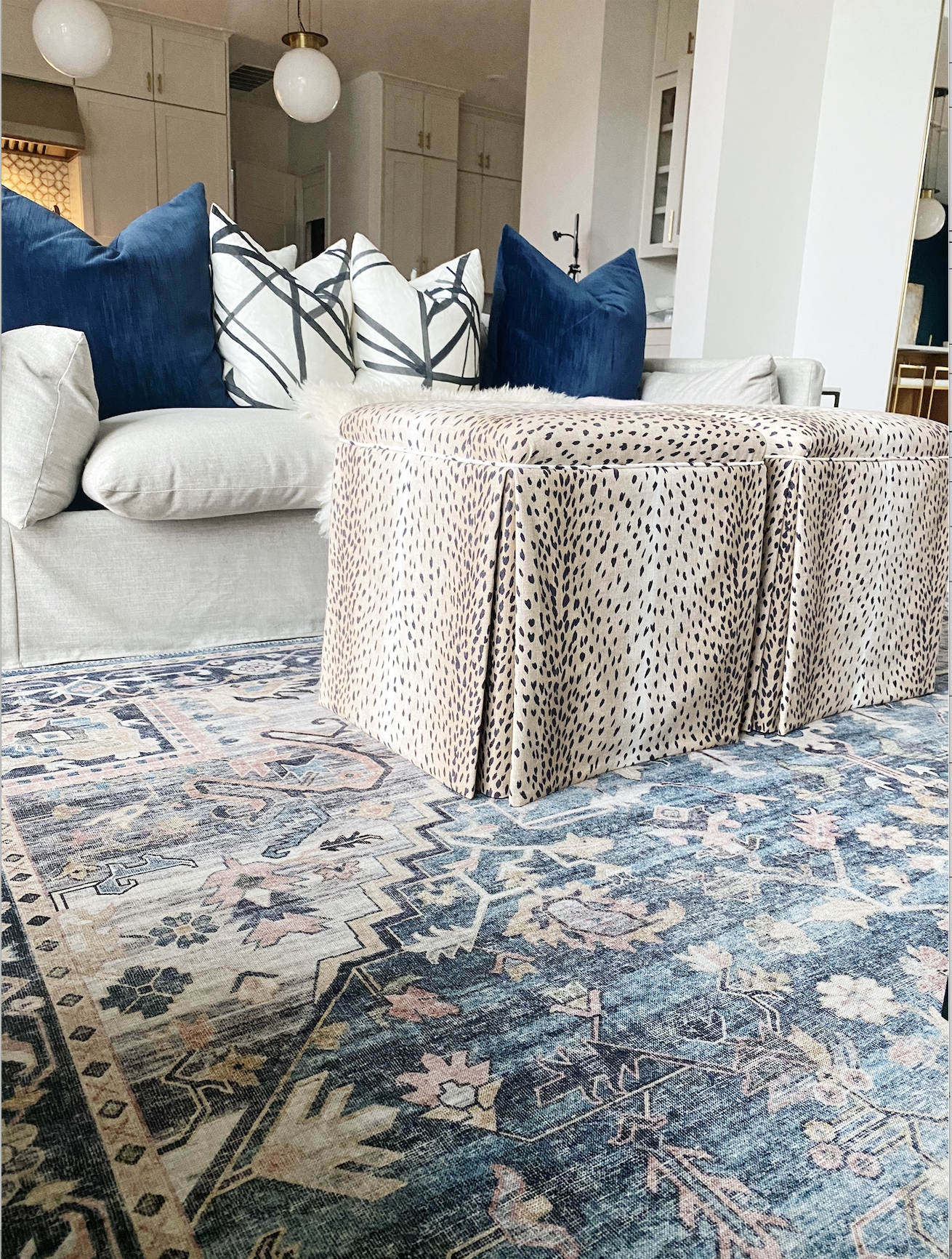 How-to-Update-Your-Rugs-for-Spring  navy Hathaway rug with antelope linen upholstered ottomans in front of a gray slipcovered sofa chair with black and white graphic pillows and navy velvet pillows