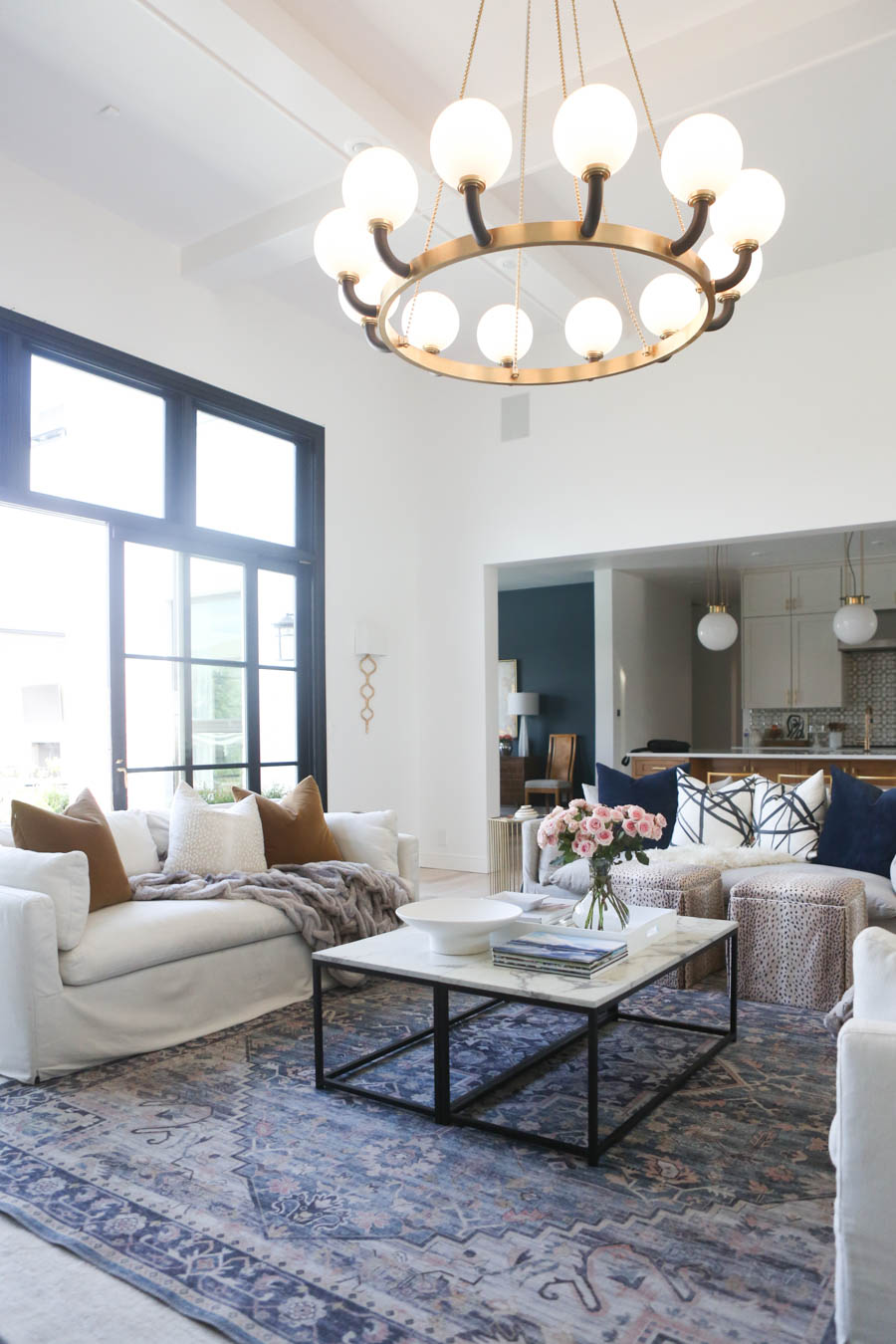 CC and MIke Living Remodel Reveal large natural wood island with quartz countertops and gold bar stools living room with navy rug slipcover crypton fabric navy Hathaway navy velvet pillows leopard ottomans marble coffee tables navy and pink large area rug
