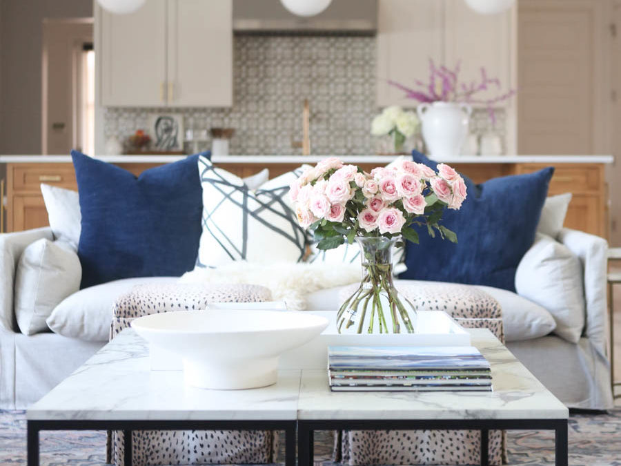 CC and MIke Kitchen Remodel Reveal large natural wood island with quartz countertops and gold bar stools living room with navy rug slipcover crypton fabric navy Hathaway navy velvet pillows leopard ottomans marble coffee tables