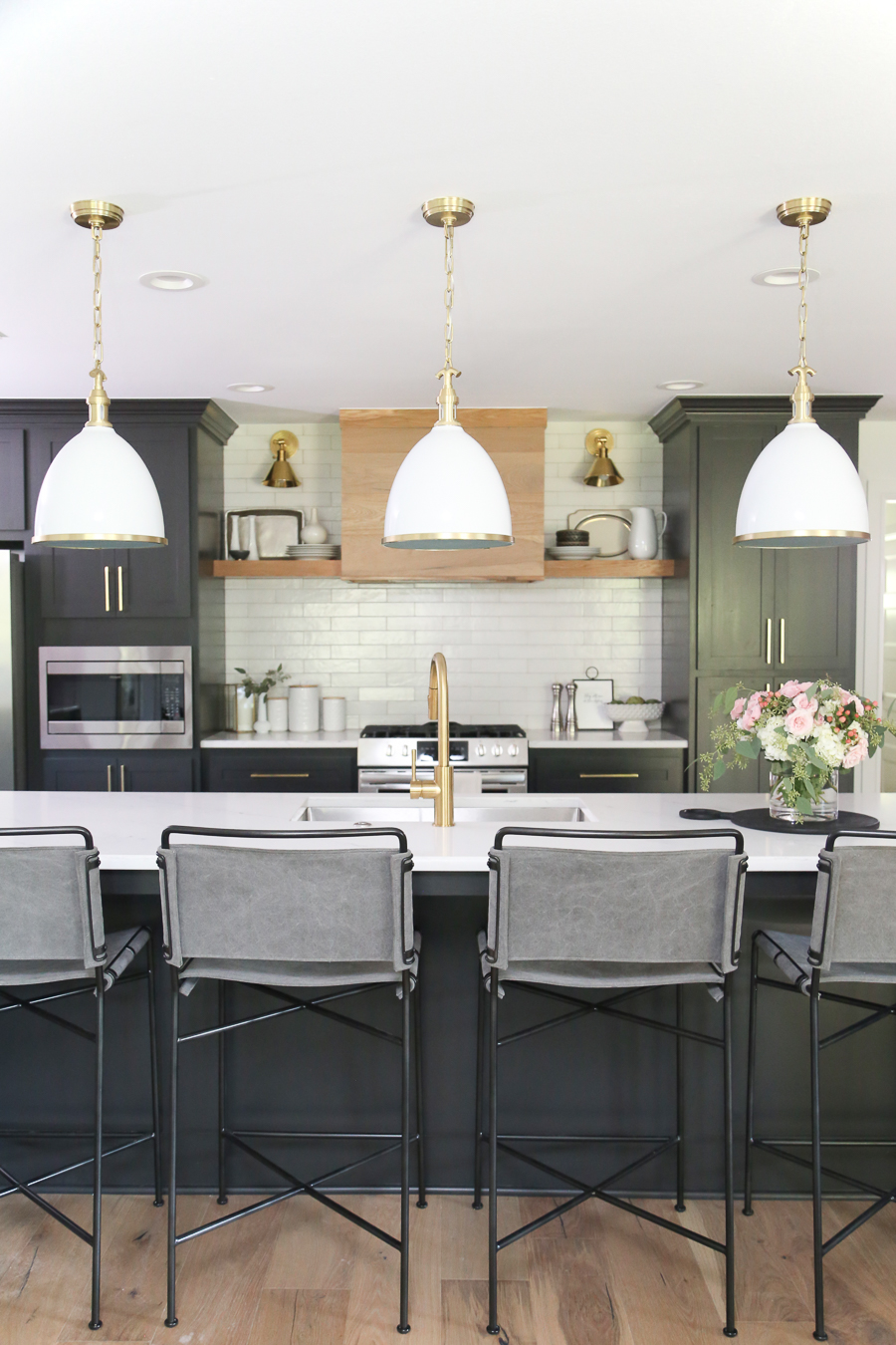 CC and Mike Modern Navy and Cedar Ranch Style Remodel navy brick with black front door and cedar posts and shutters black kitchen cabinets with gold hardware and a wood vent hood open shelving with sconces and a gold faucet with gray canvas bar stools