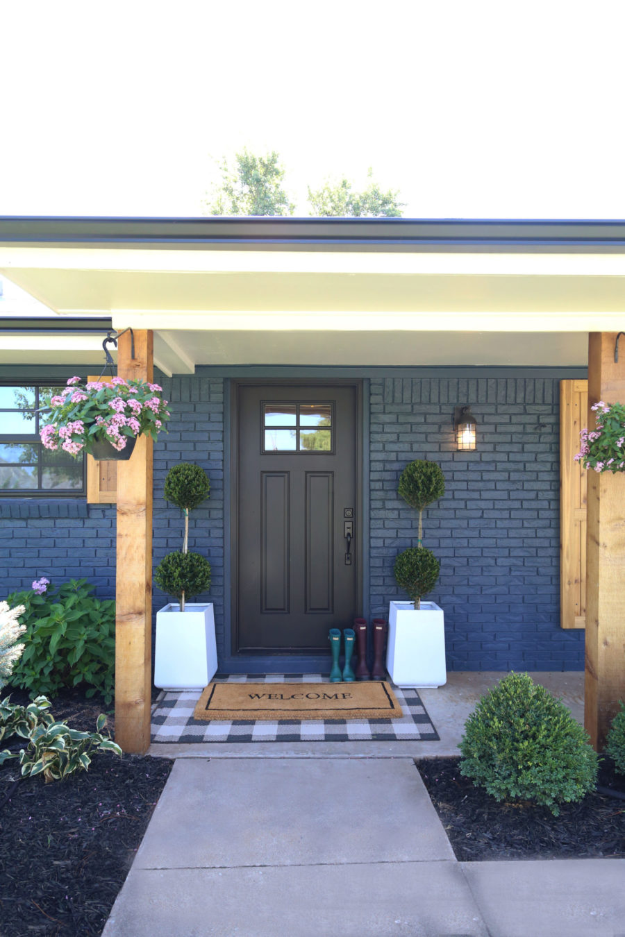 CC and Mike Modern Navy and Cedar Ranch Style Remodel navy brick with black front door and cedar posts and shutters with pink flower hanging baskets cement planters with topiaries and buffalo check rug layered on a front porch