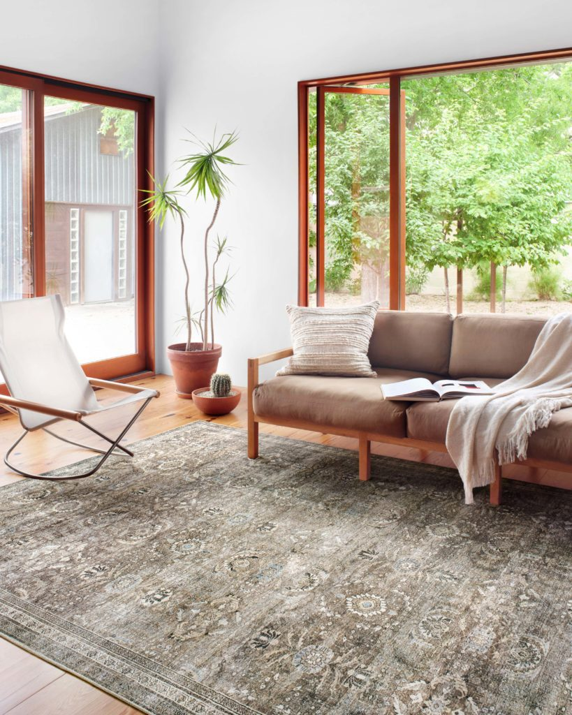 Spacious minimalist living room with moss green area rug: Layla in Antique Moss